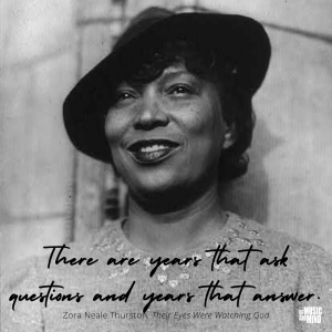 Black and white photo of Zora Neale Thurston with hat and sweater standing in front of a wall.
